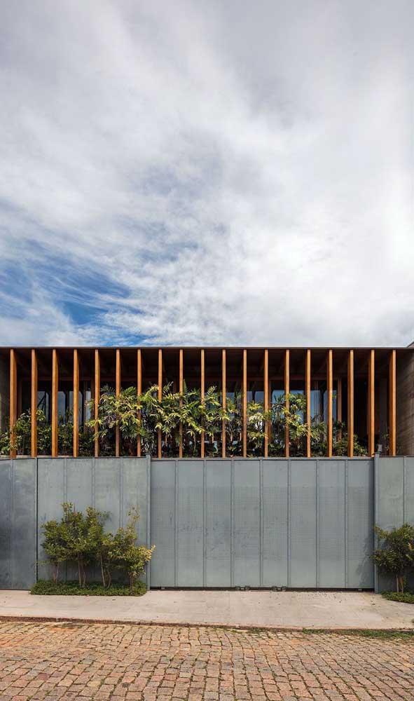 Muro e portão se confundem nessa fachada de casa moderna