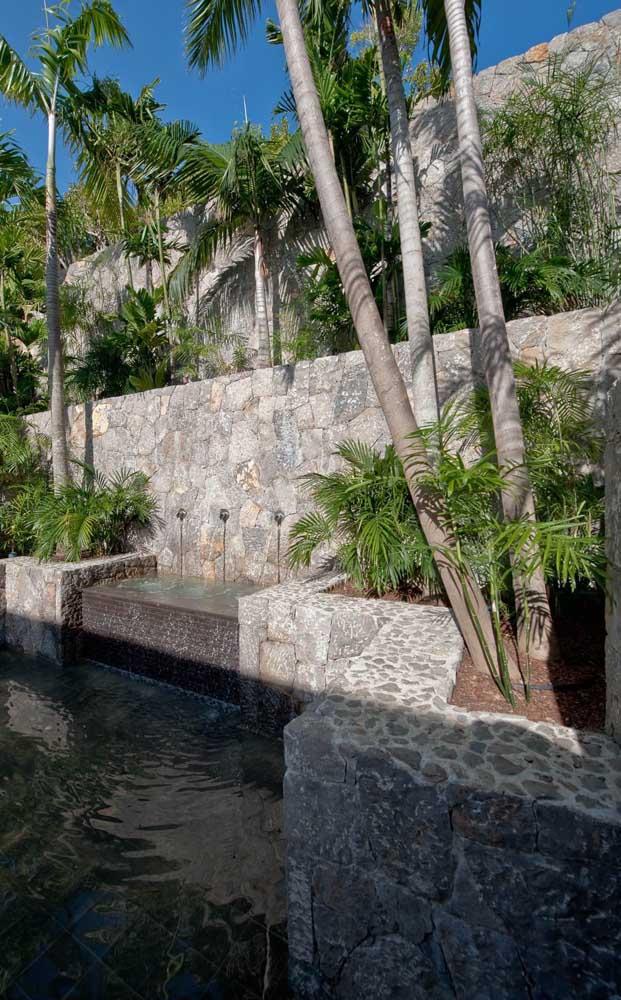 Aqui, o muro moderno de pedras ganhou um clima tropical com as palmeiras