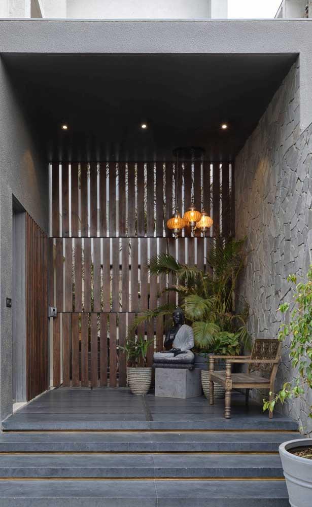 Hall de entrada com muro de pedras. Repare que a cor cinza trouxe modernidade ao projeto