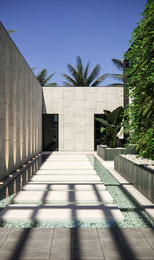 Vista interna de um muro moderno revestido com placas de pedras e iluminado indiretamente por spots de chão