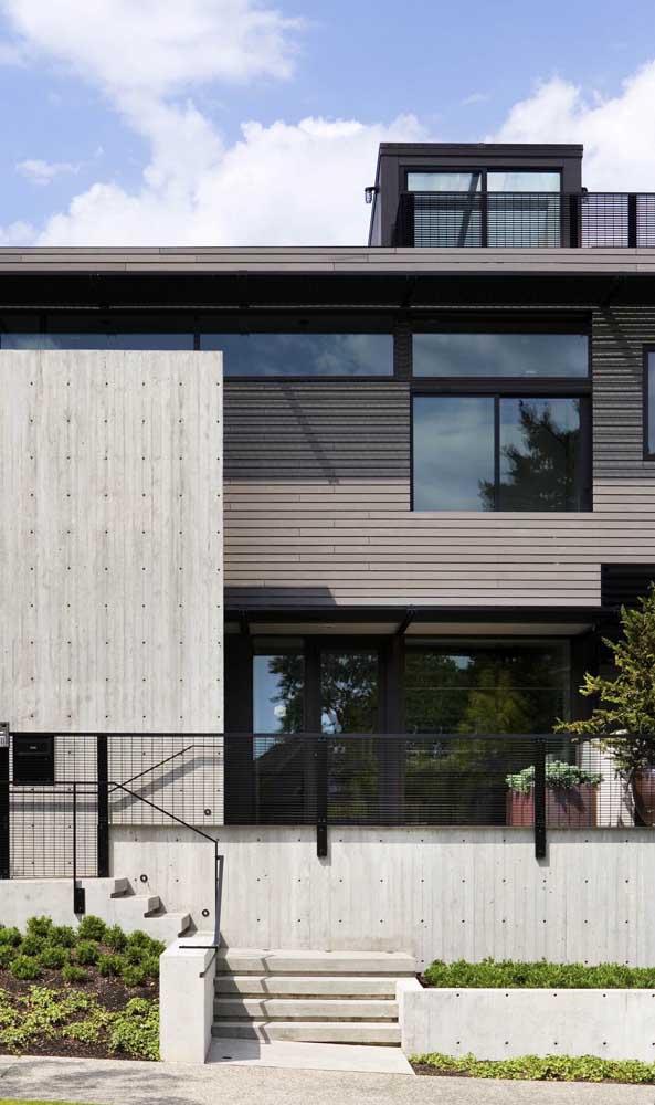 Muro moderno de concreto em tom claro para destacar a fachada que vem logo atrás em um tom mais escuro