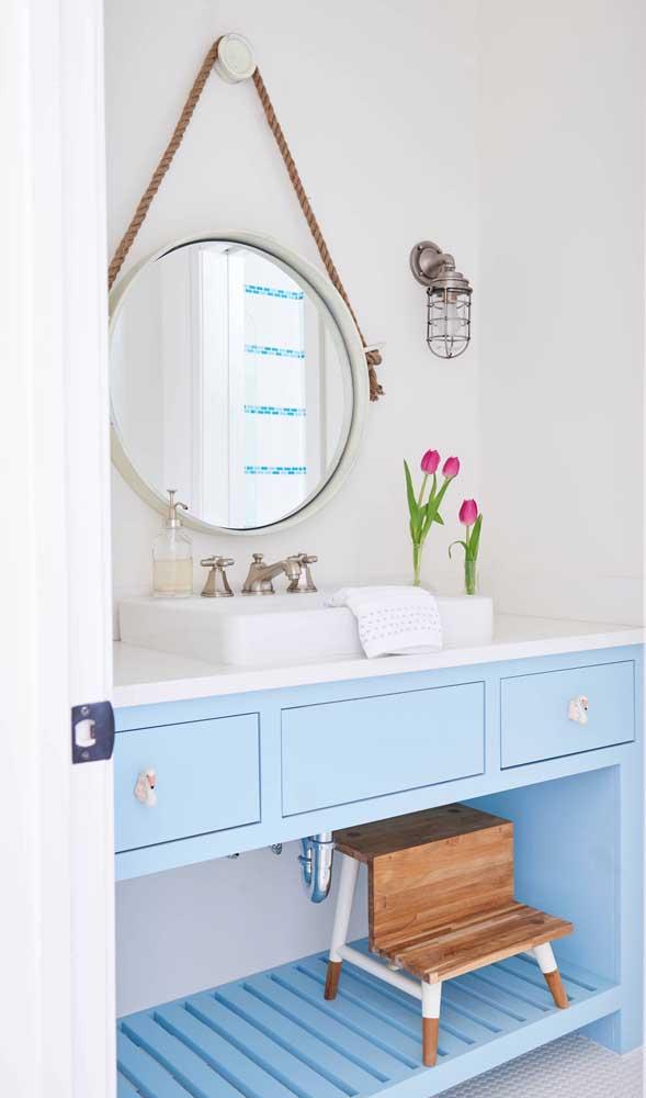 A delicadeza do banheiro em tom de azul claro casou perfeitamente com o espelho Adnet suspenso pela corda naval