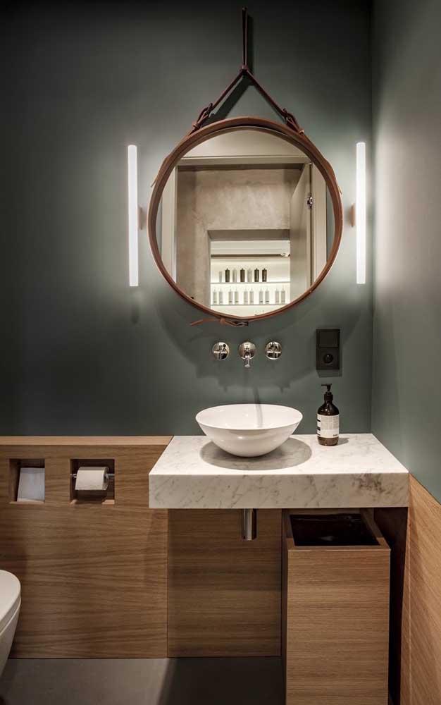 A parede verde ajuda a destacar o espelho Adnet no banheiro