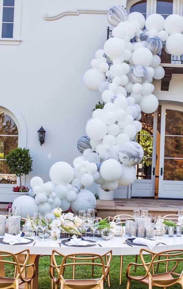 Arco de balões descontruído para decorar a festa de bodas de pérola que acontece na área externa da casa