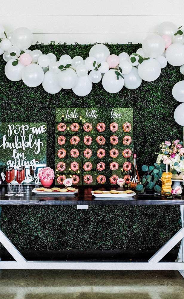 Para sair um pouco do convencional, essa festa de bodas de pérola inovou com um painel verde atrás da mesa do bolo