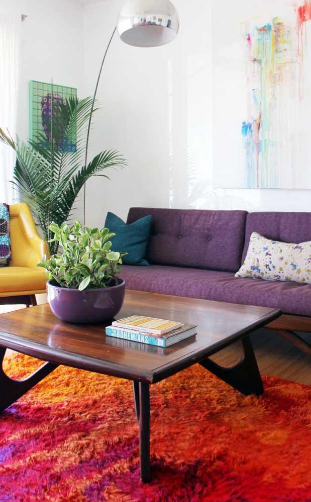 Que tal ousar um pouco mais e apostar em um sofá roxo combinado a um tapete laranja?