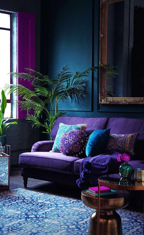 A parede azul criou o pano de fundo perfeito para o sofá roxo, garantindo profundidade ao ambiente