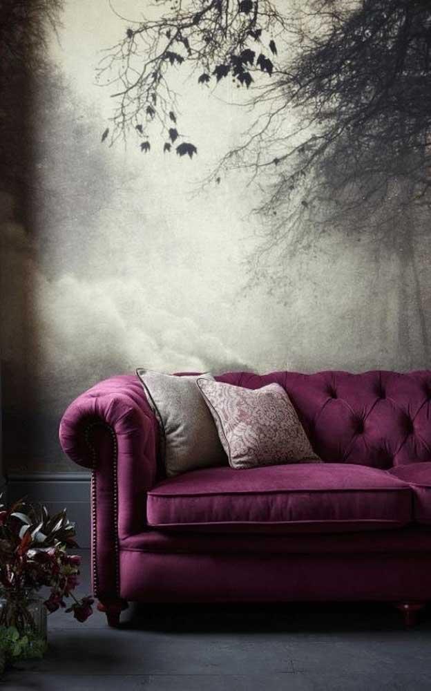 Aqui, o painel na parede reforça a sensação de mistério da cor roxa presente no sofá