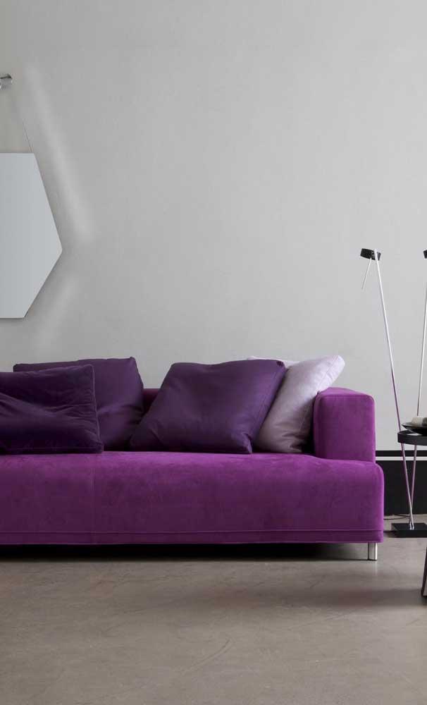 Sofá roxo com design moderno e minimalista. As almofadas criam um lindo tom sobre tom