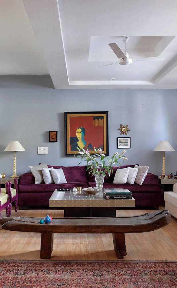 O ponto alto dessa decoração é o sofá roxo posicionado bem no centro da sala