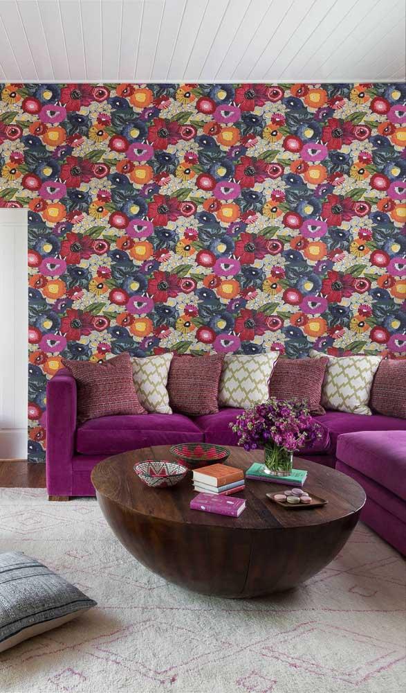 Perto do papel de parede, o sofá roxo parece até se camuflar