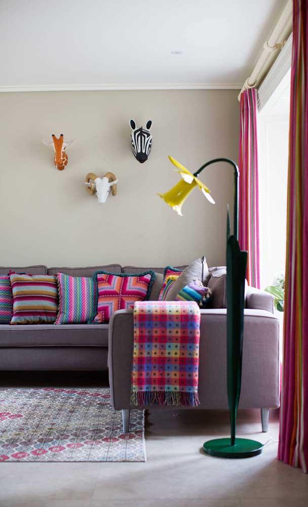 Sofá roxo claro destacado pelas almofadas e manta coloridas