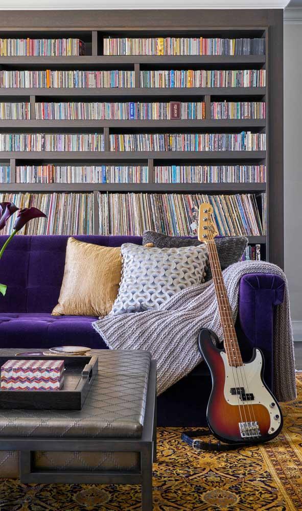 Aqui, o sofá roxo se combina aos detalhes do tapete