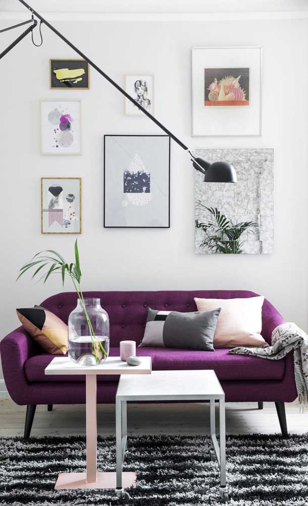 A sala de estar em tons claros apostou em um sofá roxo pequeno combinado ao tapete em preto e branco
