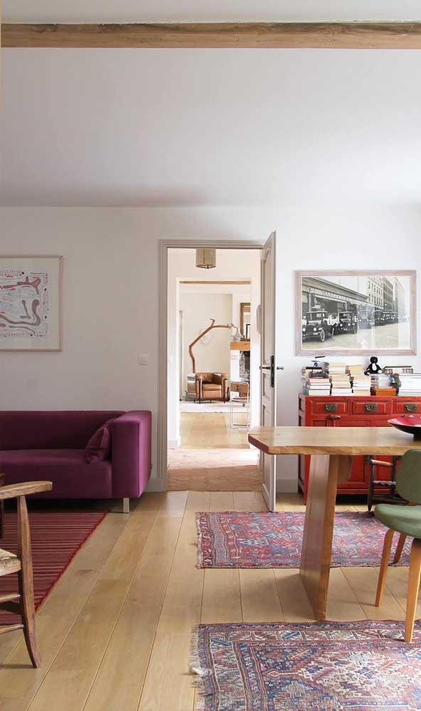 A sala integrada apostou em um sofá roxo moderno para combinar com os tapetes
