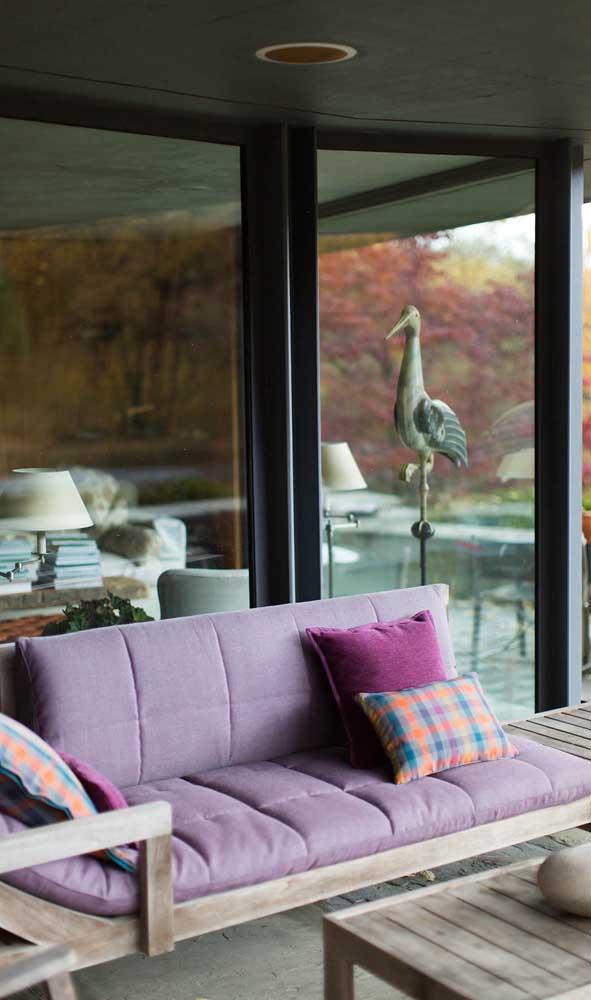 Sofá roxo com estrutura de madeira para compor a área externa da casa