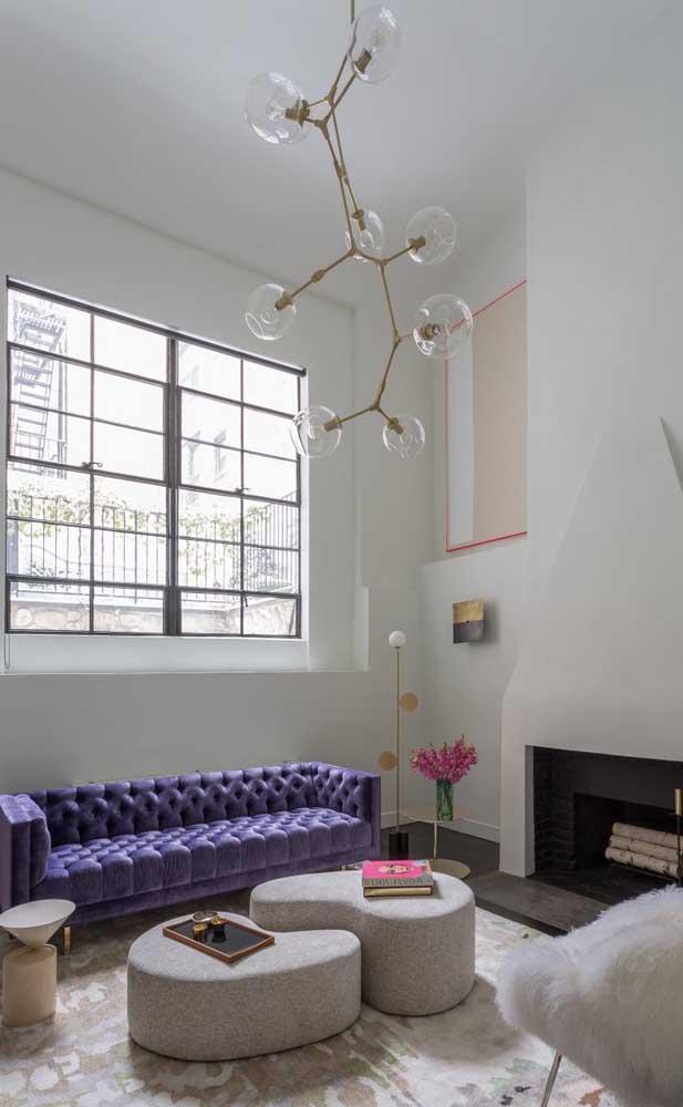 Em meio ao branco da decoração, o sofá roxo é puro destaque