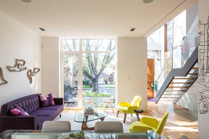 Combinação moderna e vibrante: sofá roxo com poltronas amarelas