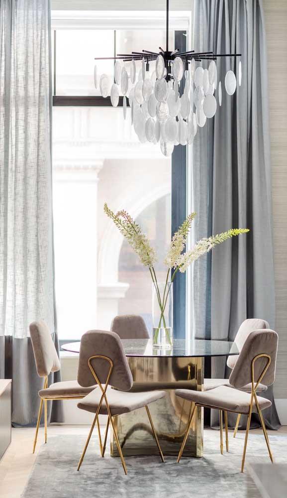 Mesa de jantar de vidro redonda com base metálica dourada combinando com os pés das cadeiras