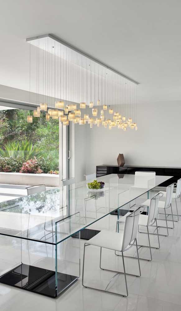 Mesa retangular de vidro com base também em vidro. Repare que a luminária acompanha o formato e a dimensão da mesa