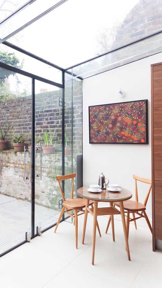 Mesa de madeira redonda com tampo de vidro sobreposto. Nesses casos, o vidro utilizado pode ter uma espessura menor