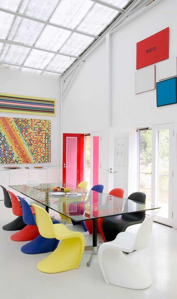 Que charme essa mesa retangular de vidro acompanhada de cadeiras pantons coloridas