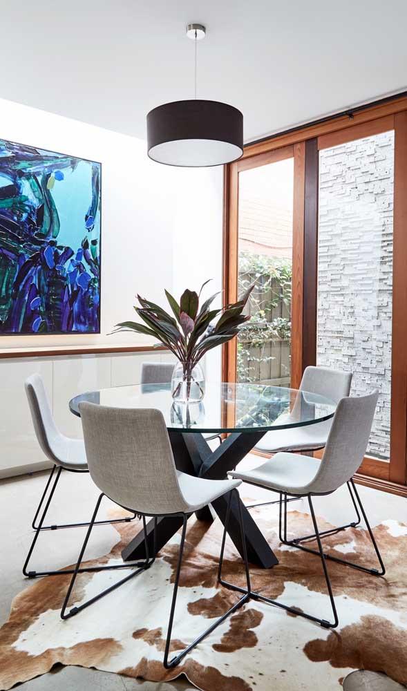 Mesa de jantar redonda de vidro com quatro lugares. Sobre ela, a luminária, também redonda