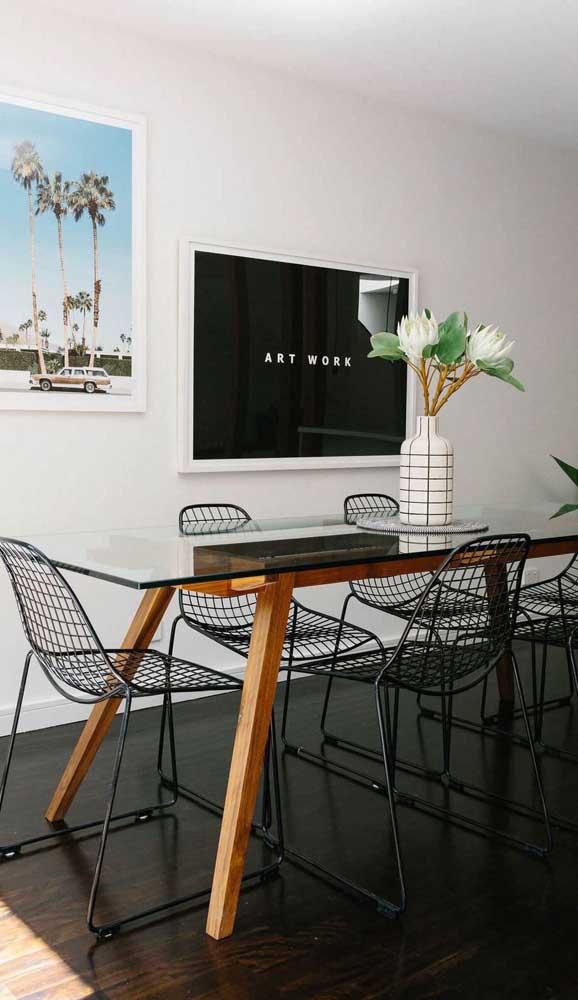 Aqui, o destaque é o contraste entre os pés de madeira da mesa de vidro com as cadeiras aramadas pretas