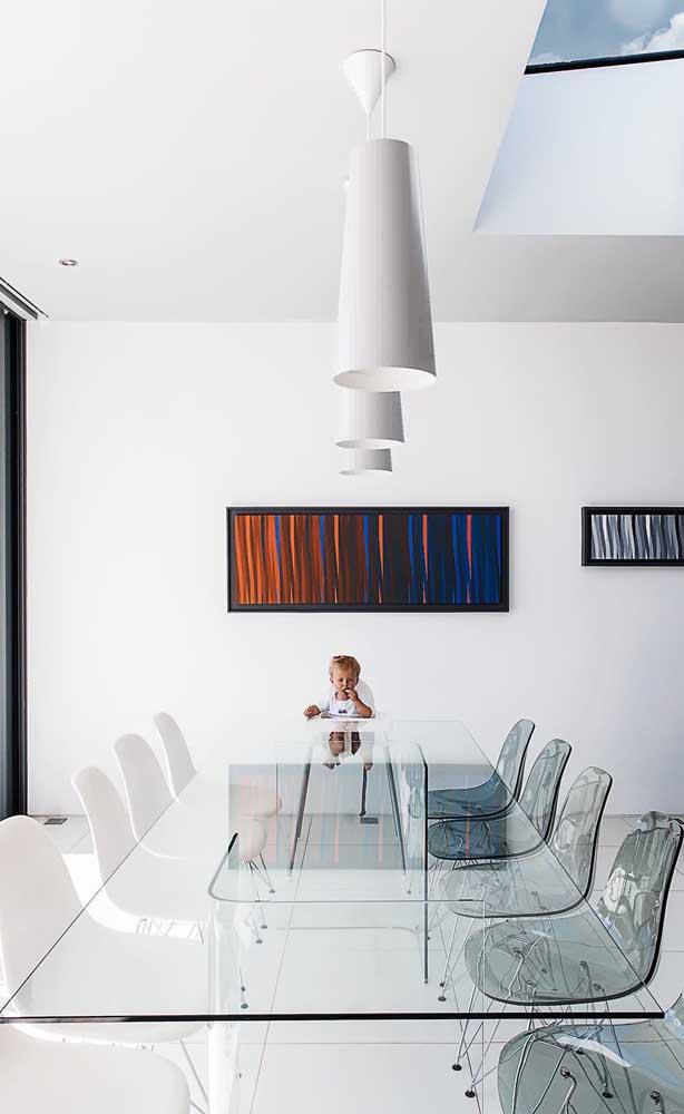 Mesa de jantar de vidro com dez lugares adornada pelas cadeiras Charles Eames