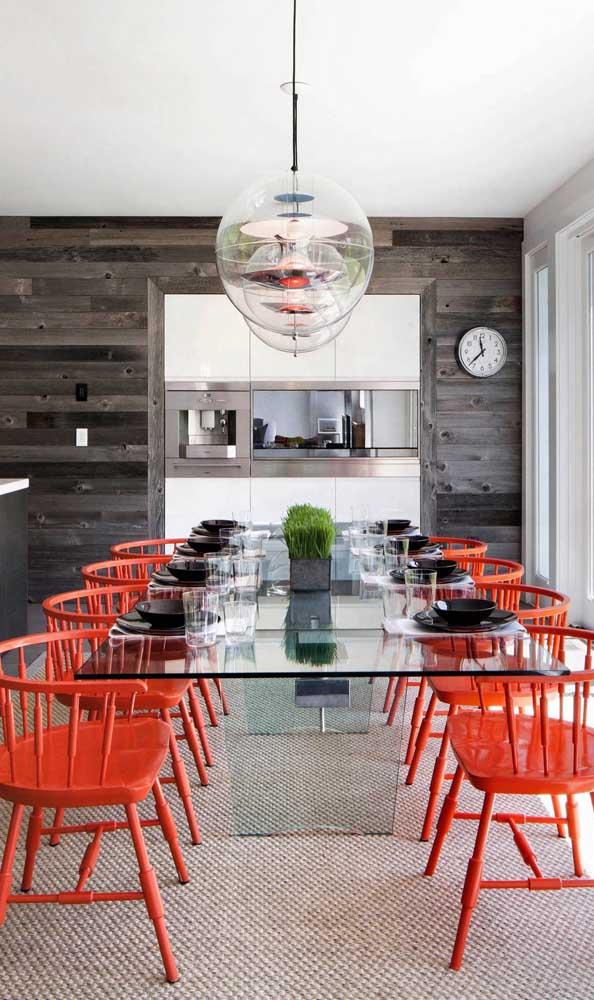 A delicadeza da mesa de vidro formou um lindo contraste com a aparência marcante das cadeiras vermelhas