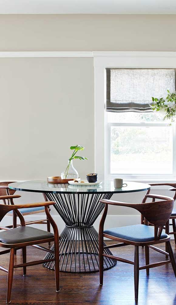 Aqui, a base metálica da mesa de vidro se contraste com a estrutura em madeira das cadeiras