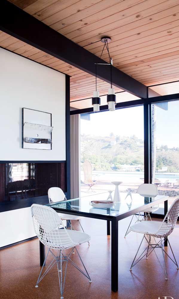 Mesa de jantar com tampo de vidro transparente e estrutura metálica preta