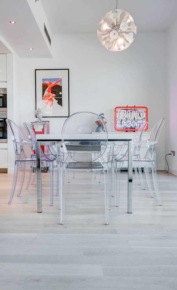 Sala de jantar moderna com mesa de vidro e cadeiras de acrílico transparente