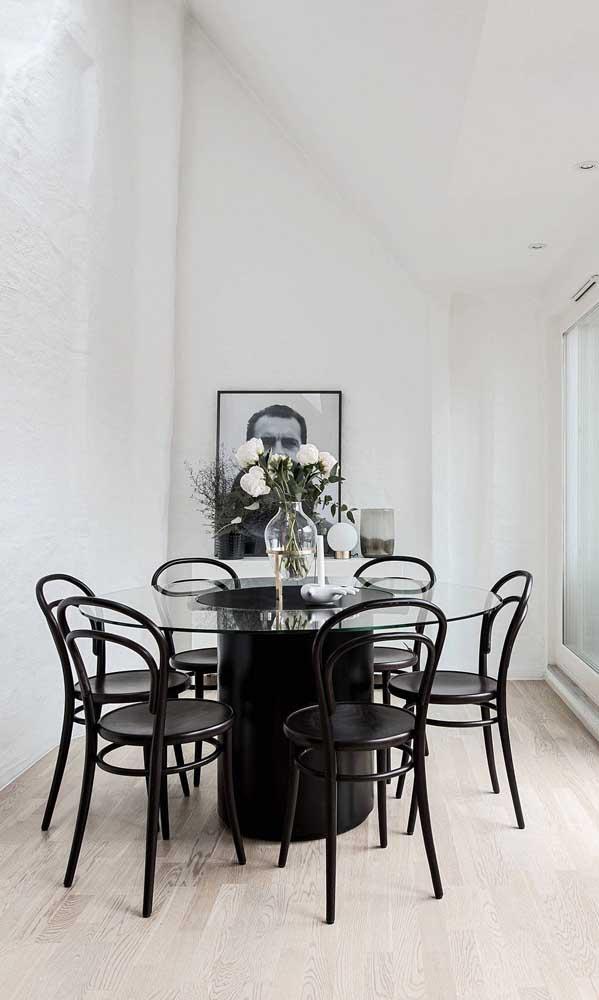 A mesa de vidro com base e cadeiras pretas é todo o destaque dessa sala de jantar branquinha