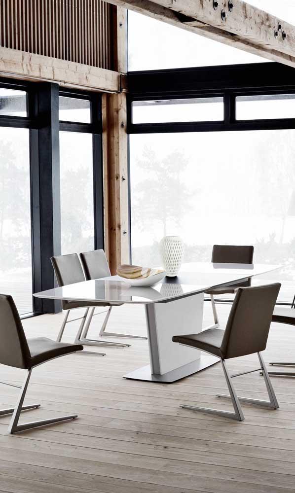Mesa de jantar com vidro branco acompanhada de cadeiras modernas em couro