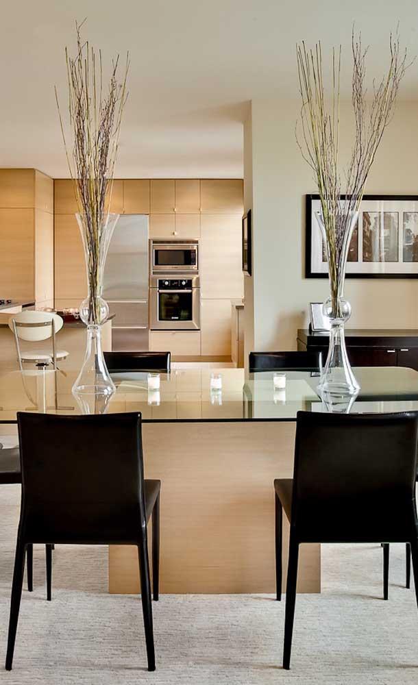 Elegante e moderna, essa mesa de vidro com base de madeira traz apenas quatro cadeiras ao seu redor