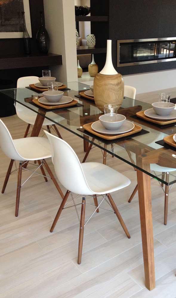 As cadeiras Charles Eames formaram a composição perfeita com essa mesa de vidro com pés de madeira