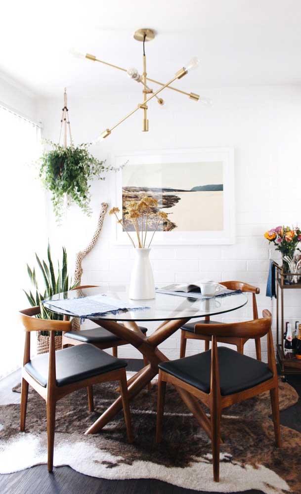 O ambiente rústico e de influência étnica apostou em uma mesa de vidro redonda com pés de madeira, assim como as cadeiras