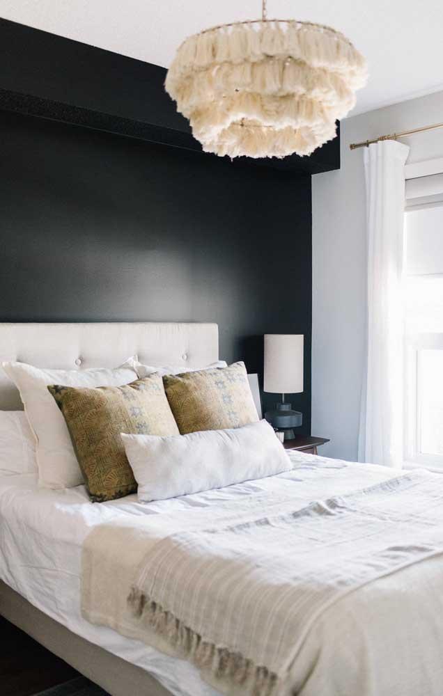 Nesse quarto de casal, a parede preta ajuda a destacar o abajur branco