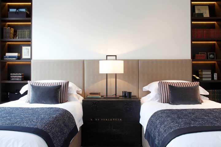 Um abajur grande entre as camas de solteiro foi o suficiente para esse quarto