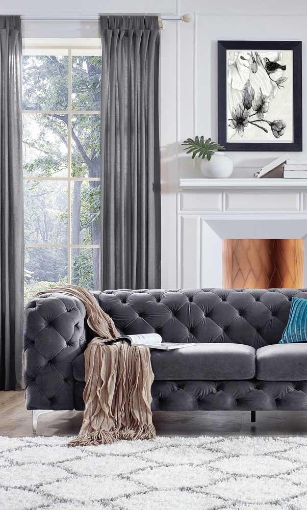 A cor cinza trouxe sobriedade e elegância na medida certa para esse sofá Chesterfield