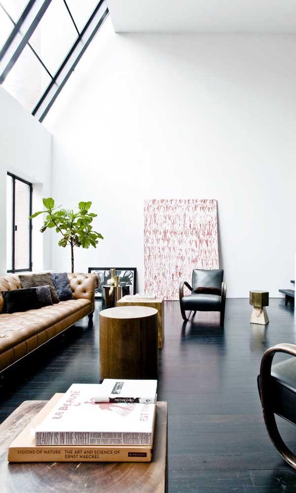 Sala de estar decorada com sofá Chesterfield amarelo. Quadros e almofadas finalizam a proposta