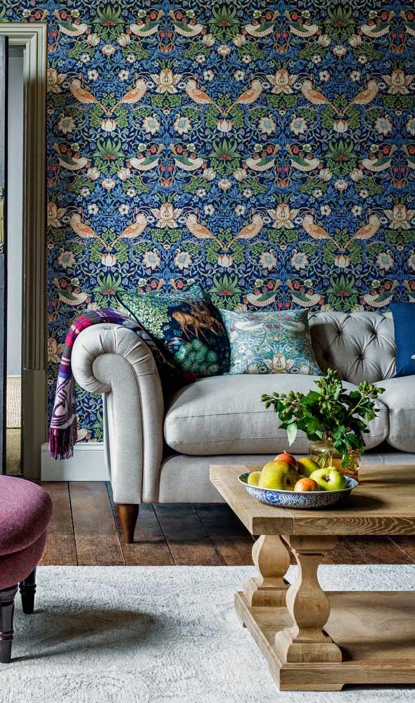 Aqui, o papel de parede florido contracena harmoniosamente com o sofá Chesterfield de couro claro