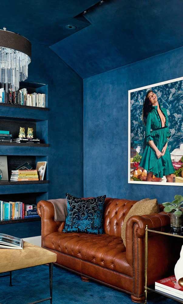 Super contemporânea, essa sala de estar não teve medo de ousar e investiu no contraste entre a parede toda pintada de azul com o Chesterfield de couro caramelo
