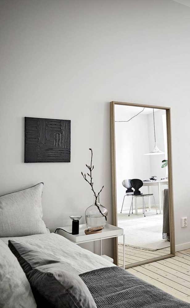 Espelho grande retangular com moldura simples de madeira apoiado no chão do quarto