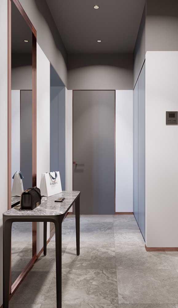 O espelho grande no hall amplia e ilumina o corredor da casa