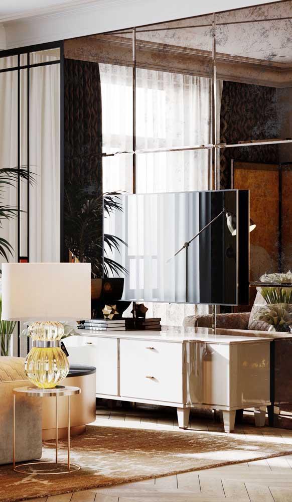 Espelho grande cobrindo toda a parede da sala de estar; atenção redobrada para não deixar fios refletidos