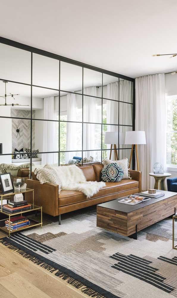 Na parede atrás do sofá, o enorme espelho traz luz e amplitude