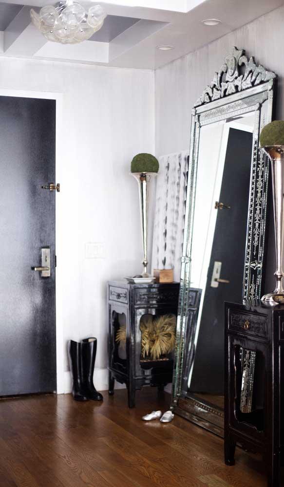 Hall de entrada com espelho grande veneziano usado de modo bem moderno, apenas apoiado no chão
