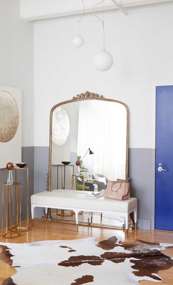 Espelho grande com moldura dourada combinando com os demais elementos decorativos
